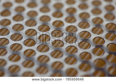 Grid with round perforation. Metal holes on an orange background. Oil filter close-up.
