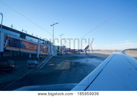NUREMBERG, GERMANY - JAN 20th, 2017: Aircraft window view of the Nuremberg airport apron airport terminal with airplanes parked to gates airport trucks air traffic control tower on background.