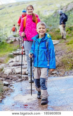 Happy hiking boy with trekking sticks in the mountains with his sister. Norway