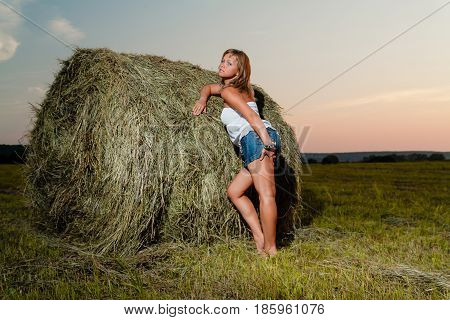 Young beautiful blonde with tanned legs posing near a haystack against a summer sunset background