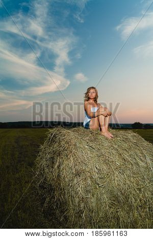 Young beautiful blonde with tanned legs posing on a haystack against a summer sunset background