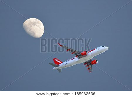 Faro Algarve Portugal - October 29 2015 : Easyjet Airbus A320 aircraft taking off from Faro Airport with a three quarter moon in the evening sky