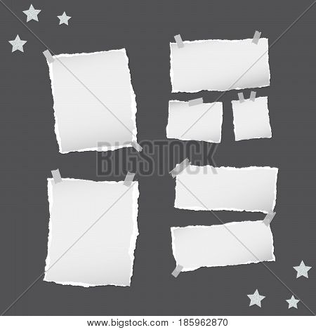 Ripped white note, notebook, copybook paper sheets, stars, stuck with sticky tape on black background