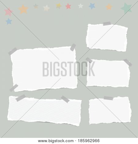 Ripped white note, notebook, copybook paper sheets, stars, stuck with sticky tape on gray background