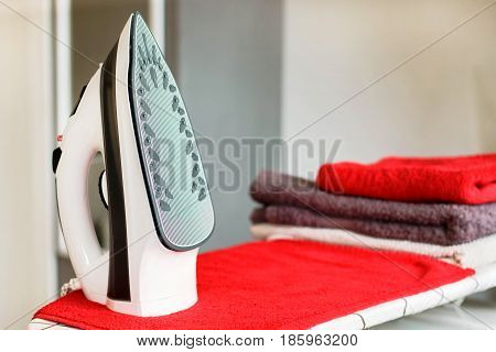 Iron for ironing on the ironing board with a pile of towels near