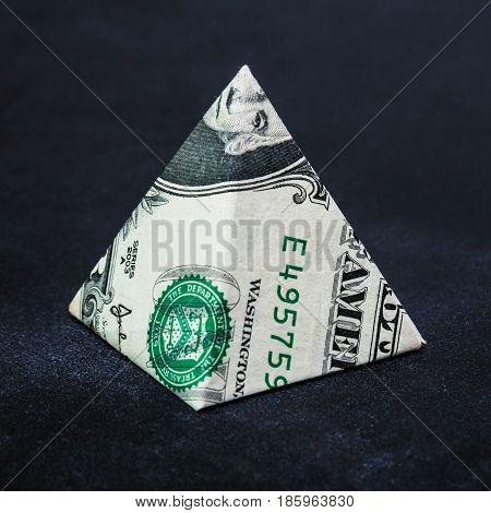 Origami dollar pyramid money symbol business on a black background