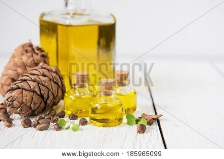 Oil of cedar nuts on a white wooden background