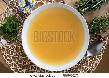 Bone broth made from chicken served in a white plate with chopped parsley green herbs and flowers in the background