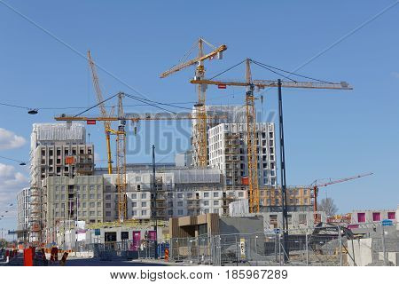 STOCKHOLM SWEDEN - MAY 01 2017: Cranes building houses in the new district New Hagastaden in Stockholm. May 01 2017 in Stockholm Sweden