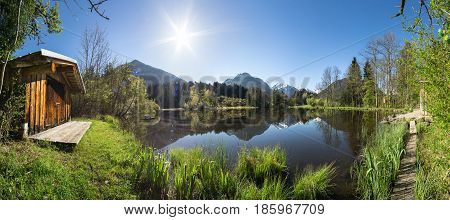 Log cabin at alpine lake with early morning sunlight. Nice reflections of snow-capped mountains in the water of the lake. Bavaria, Germany, Alps.