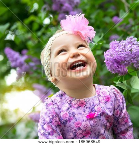 Beautiful little girl playing in spring park, lilac flowers garden. Childhood. Cute kid's face over nature background. Cheerful child's portrait, soft focus.
