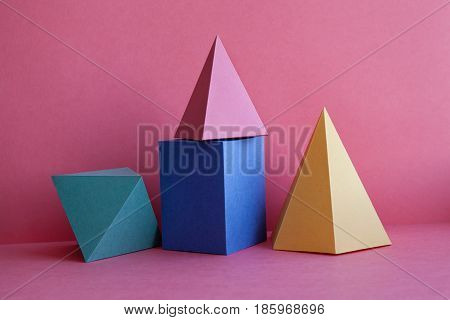 Platonic solids abstract geometric still life composition. Prism pyramid rectangular cube figures on pink paper background. Yellow blue pink green color.