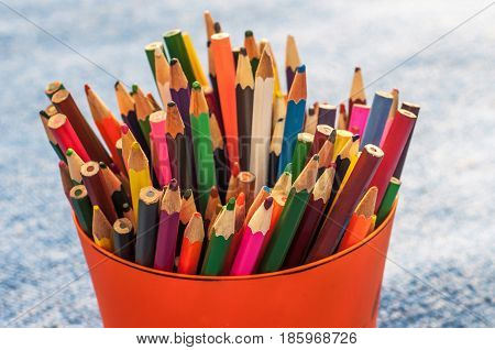 A pail with pencils on a light blue background