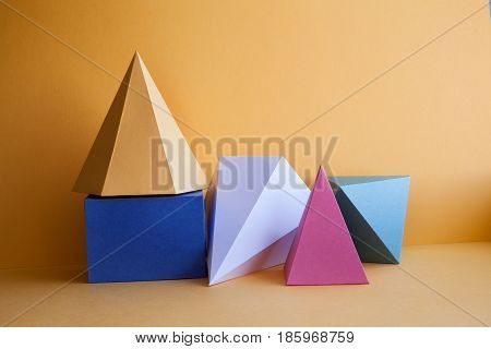 Platonic solids abstract still life composition. Prism pyramid rectangular cube figures on yellow paper background. Yellow blue white green color geometric objects.