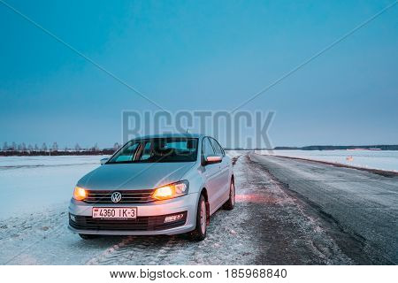 Gomel, Belarus - January 26, 2017: Volkswagen Polo Car Sedan Parking On A Roadside Of Country Road On A Background Of Blue Sky At Winter Season