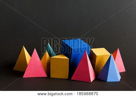 Colorful abstract solid figures composition. Three-dimensional prism pyramid rectangular cube geometric objects on black paper background. Red blue yellow green colored, soft focus photo