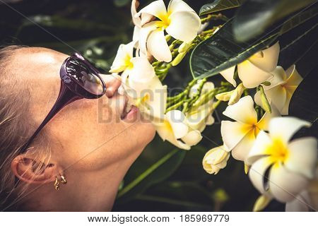 Young beautiful woman smelling tropical flowers during her travel vacation