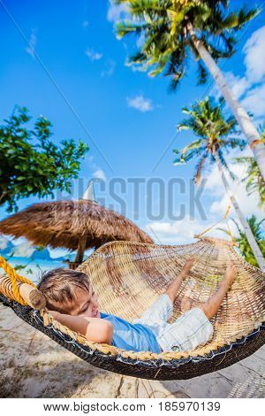 Cheerful little boy relaxing on a tropical beach in hammock.