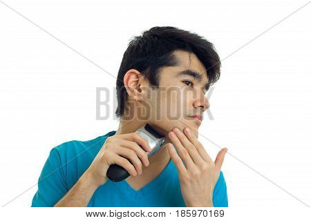 young guy with black hair turned his head to the side and shaves the beard trimmer is isolated on a white background
