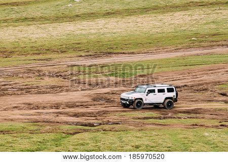 Stepantsminda Gergeti, Georgia - May 23, 2016: White Hummer H2 SUV Car On Off Road In Spring Mountains Landscape In Georgia. Landscape Of Gorge At Spring Season.
