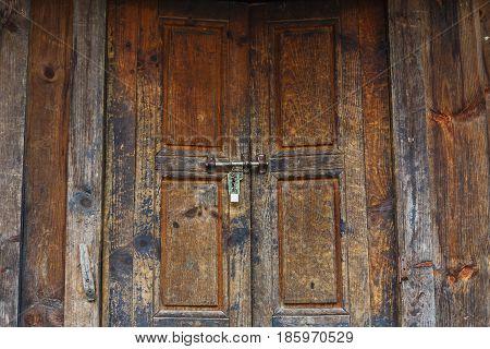Old textured wooden brown door with a lock