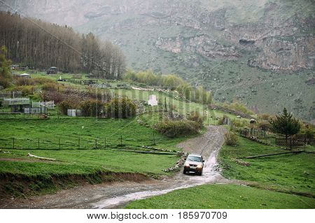 Kazbegi, Gergia - May 23, 2016: Mitsubishi Montero Sport SUV car driving on country road in summer meadow. Mitsubishi Pajero Sport is a mid-size SUV produced by Japanese manufacturer Mitsubishi Motors