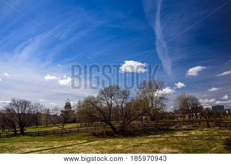 Spring park Kolomenskoye, former royal estate, with silhouette of a wooden ancient Orthodox Church of St. George the Victorious on the background, Moscow, Russia