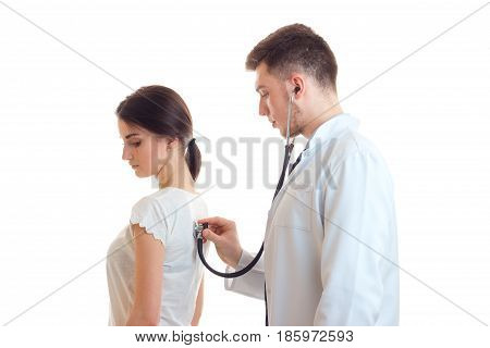 a young doctor in a white lab coat stethoscope listens back girl isolated on white background