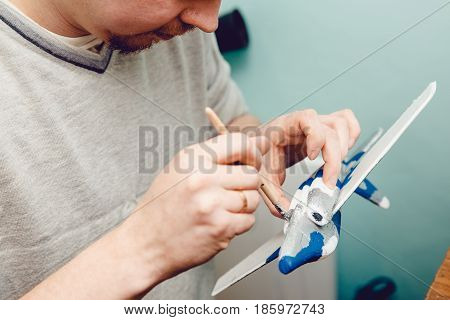Aircraft on the radio control, the man paints the fuselage