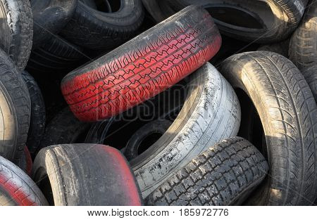 Close up of red car tires with tread in a pile of used tires