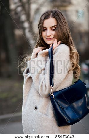 Portrait of smiling gorgeous woman wearing in beige coat holding leather handbag and looking down over shoulder. Stylish street look. Beautiful girl with wavy hair walking in spring park and posing.