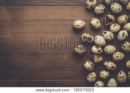 many quail eggs. quail eggs on the brown table. quail eggs on wooden background. quail eggs background with copy space