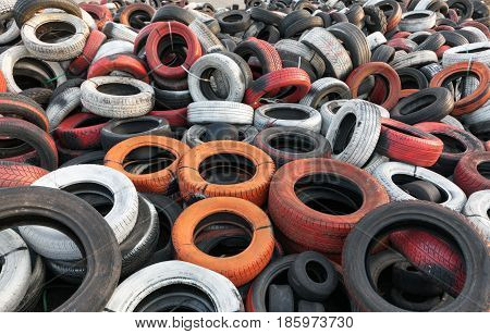 Variety of red white orange and black waste car tires piled in a big pile