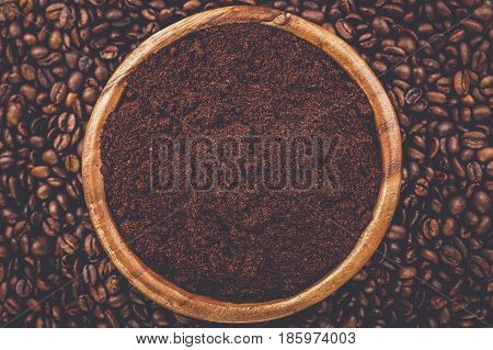 coffee beans and wooden bowl full of ground coffee on the table background