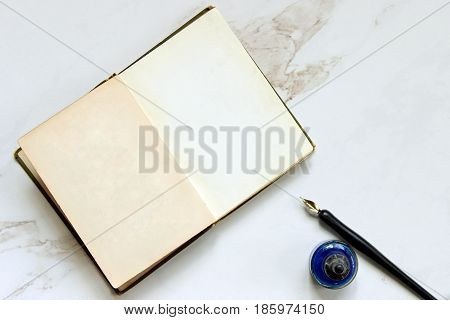 Vintage book open to blank pages with pen and ink. Copy space.