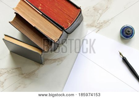 Vintage books stacked on white marble desk with pen, ink and blank white paper.