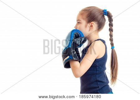 little girl with pigtail stands sideways to the camera in boxing gloves is isolated on a white background