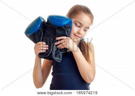 sweet girl holding a big boxing gloves is isolated on a white background