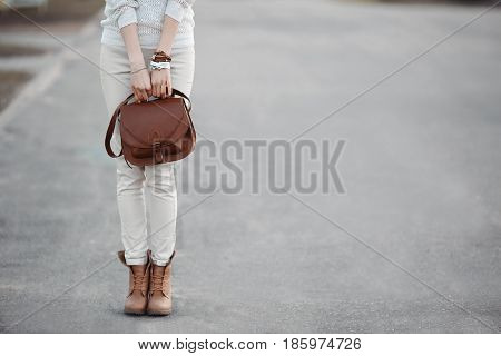 Crop of stylish incognito woman look wearing in white with red leather handbag and boats. Fashionable female walking, standing on street, posing at road. Concept of swag style and street fashion.