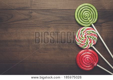 three colorful sugar lollipops on the wooden table with copy space