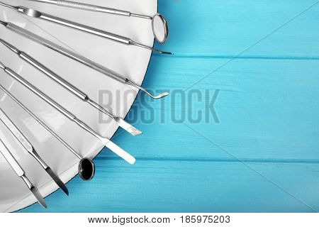 Set of dentist tools on tray against wooden background