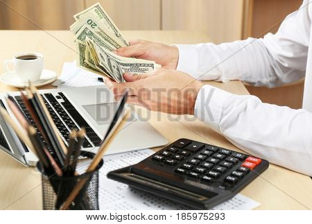 Man sitting at table and counting money, closeup