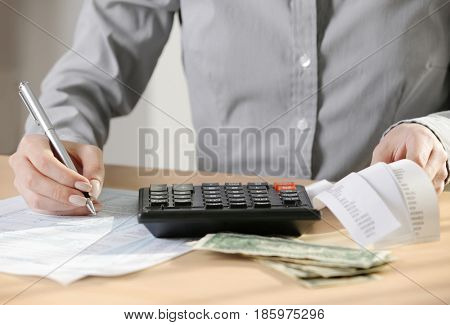 Woman filling individual income tax return form, closeup