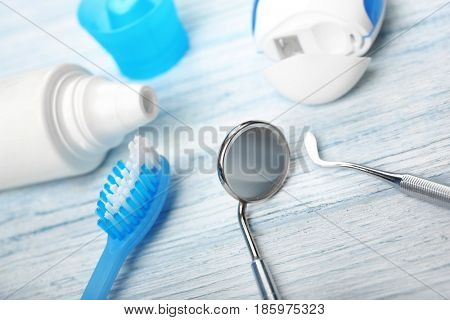 Dental tools with tooth brush, paste and floss on wooden background