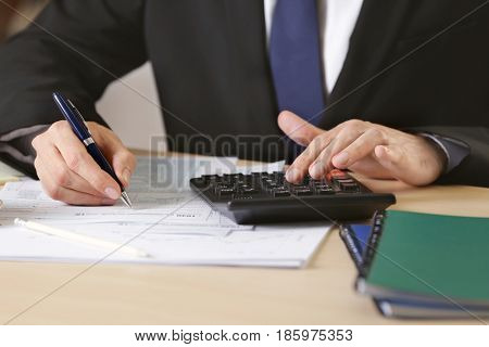 Man filling individual income tax return form, closeup