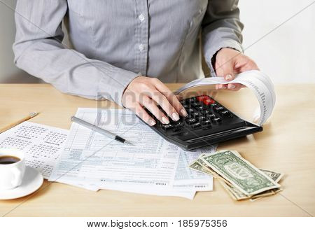 Female hands with bill and calculator, closeup