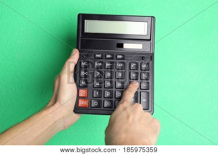 Male hands with calculator on color background