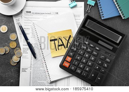 Paper sheet with text TAX, notepad, calculator and individual income tax return form on table