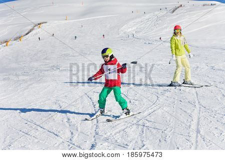 Little boy learning downhill skiing with female instructor