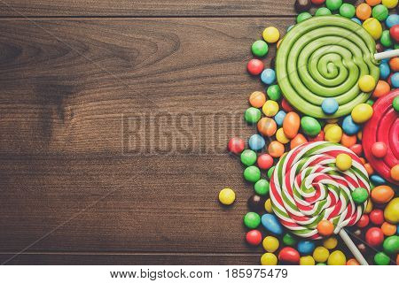 different colorful sweets and lollipops. colorful sweets and lollipops on the brown table. colorful sweets and lollipops on wooden background. colorful sweets and lollipops background with copy space